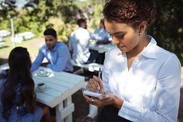 Waitress writing order on notepad