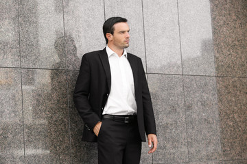Handsome man in elegant black suit standing near wall outdoors