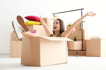 Young happy woman having fun while packing in room