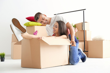 Young happy couple having fun while packing in room
