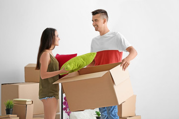 Young happy couple with cardboard box in room