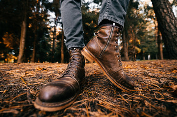 Man`s legs in woodcutter vintage leather boots and cropped jeans standing in autumn forest on ground. Fall colors and mood concept. Comfortable shoes. Walking on weekend on nature. Lens distortion.