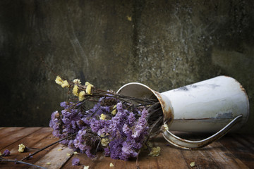 Dried flowers in old vases are left on wooden table, still life image and select focus.