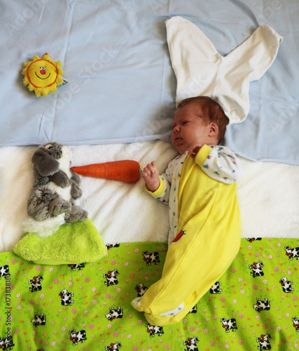 62ea528090a Cute newborn baby in bunny costume feeding bunny toy with a carrot ...
