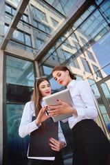 two young business women manager in classic office clothes looking at computer tablet and talking.