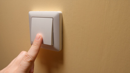 Human hand turn off a power button on a yellow wall - side view