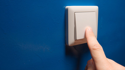 Human hand turn off a power button on a blue wall - side view