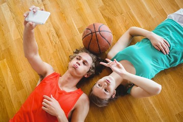 Overhead view of playful friends taking selfie while lying on