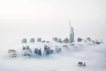 World's tallest skyscrapers surrounded by dense fog on a winter morning. Dubai, UAE.