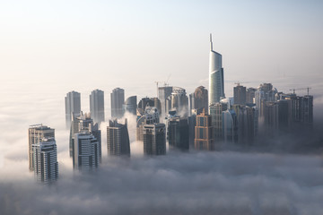 Tuinposter Dubai World's tallest skyscrapers surrounded by dense fog on a winter morning. Dubai, UAE.
