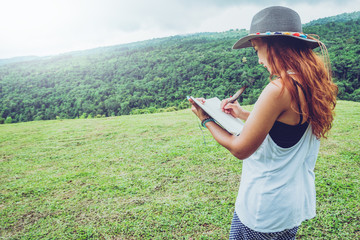 Asian women relax in the holiday. Stand write the record on grassland in the park.