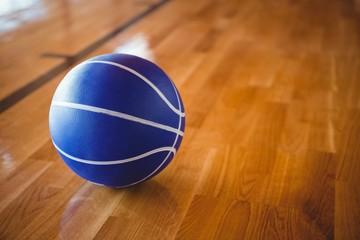 Close up of blue basketball on hardwood floor
