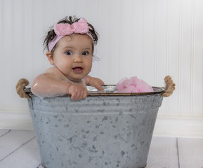 Baby girl with pink headband soaking in metal bath tub