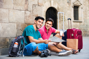 Men tourists are walking with suitcases in unknown city.