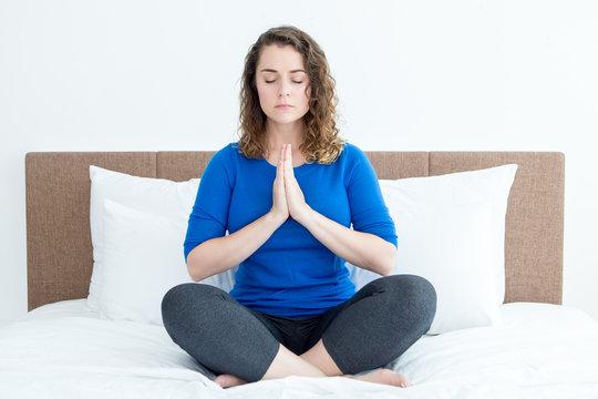 Beautiful Woman Meditating in Lotus Pose on Bed