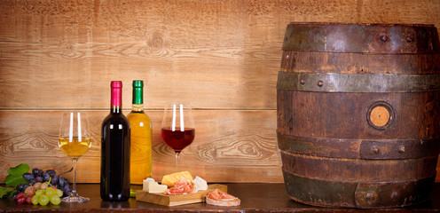 Still life with bottles and glasses of red and white wine with cheese, prosciutto and grape in wine cellar, old wine barrel. Food and drinks concept