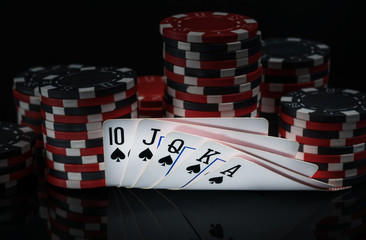 winning combinations of cards on the background of chips for playing poker in the dark