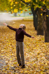 Young teenage girl throws up an armful of yellow leaves in an autumn park