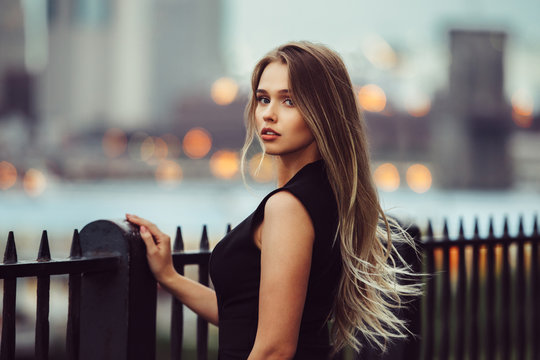 Gorgeous young model woman with perfect blonde hair looking at camera posing in the city wearing black evening dress.
