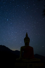 Night scape with beautiful stary sky and buddha image stand at the high mountain. Space background.
