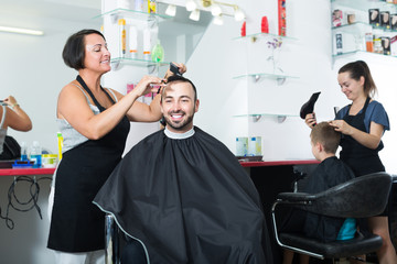 Smiling woman hairdresser cutting male client
