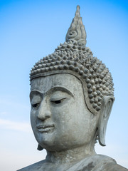 Close up face of Buddha statue with clear blue sky.