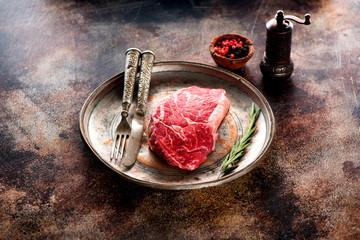 Wall Mural - Raw steak ribeye with rosemary and spices on a metal plate