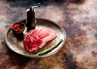 Wall Mural - Raw steak ribeye with rosemary and spices on a metal plate and copy space for text