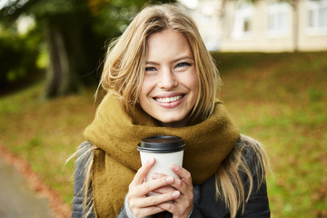 Smiling beauty with coffee in park, portrait
