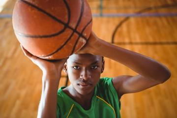High angle view of teenage boy practicing basketball