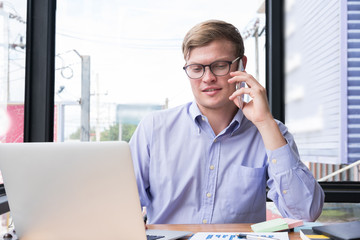 businessman talk on mobile phone at office. young man call on smart phone  at workplace. employee use cellphone at work. business communication, lifestyle concept