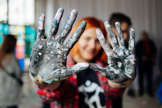 Young person showing hands covered with paint during mass art therapy session