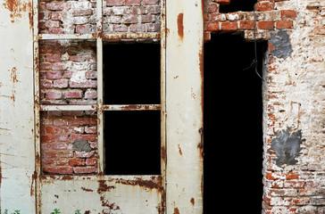 Muro antico di mattoni con porta arrugginita