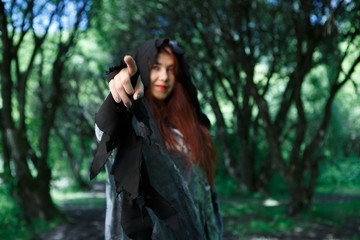 Witch points finger in forest