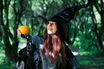 Picture of cheerful witch in hat with pumpkin