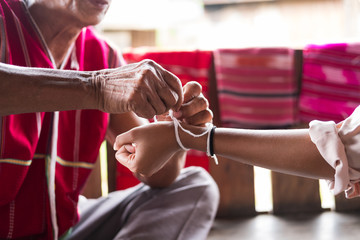Unidentified elder man from Karen ethnic hill tribe minority tie guest's wrist for blessing in tying ceremony
