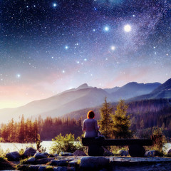 Lake Strbske pleso in High Tatras mountain, Slovakia, Europe. Fantastic starry sky and the milky way. The girl sits on a bench and looks into the fairy-tale sky.