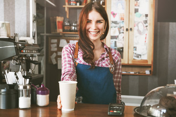 Fototapeta Young female barista smiling, while serving a coffee at the counter obraz
