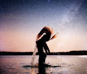 woman on water background at night sky. Fantastic starry sky and the milky way
