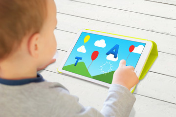 Child play game with letters on a tablet. Modern app for developing children's abilities.