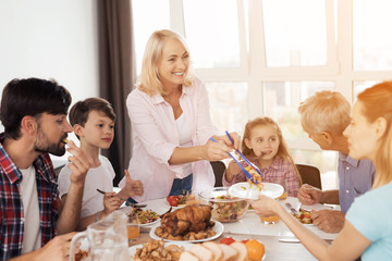 The family eats at the festive table for Thanksgiving. A woman is laying out food, her family is already eating