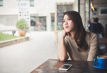 Asian beautiful woman sitting in coffee shop cafe, looking and waiting for friends, feeling lonely, sad, upset