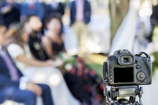 Full Frame reflex DSLR camera over tripod recording the wedding ceremony