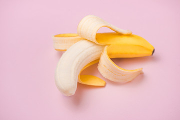 Fresh peeled banana on pink background