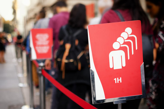 One hour waiting queue at the entrance of the Cinema Museum (Mole Antonelliana) in Turin, Italy, with tourists and waiting time  signboard