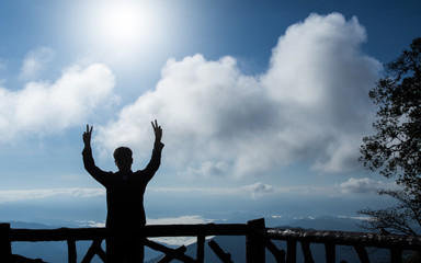 silhouette of man making peace gesture two hands, mountain and sky background