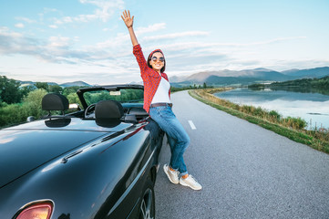 Happy smiling young woman stay near the cabriolet car on the mountain road