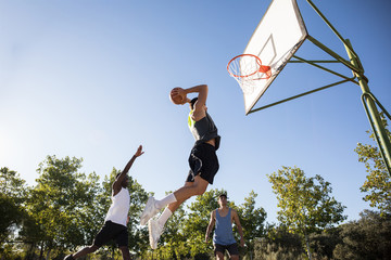 Friends playing basketball against clear sky
