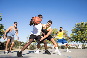 Young multiracial people playing streetball and dribbling ball on sports ground in sunlight.