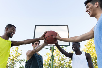 Group of diverse young men holding basketball all together while posing on sports ground.